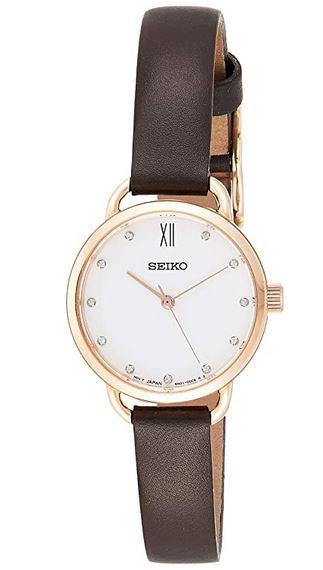 montre analogique Seiko pour femme avec cadran blanc boitier dore et bracelet fin en cuir marron