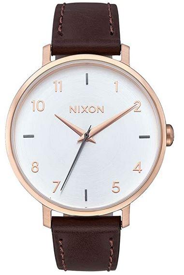 montre pour femme Nixon bracelet en cuir marron fonce boitier dore et cadran sur fond blanc modele A10912369 00